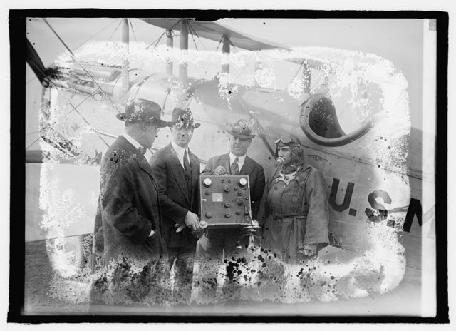[Group with instrument standing next to airplane, U.S.M [...]]