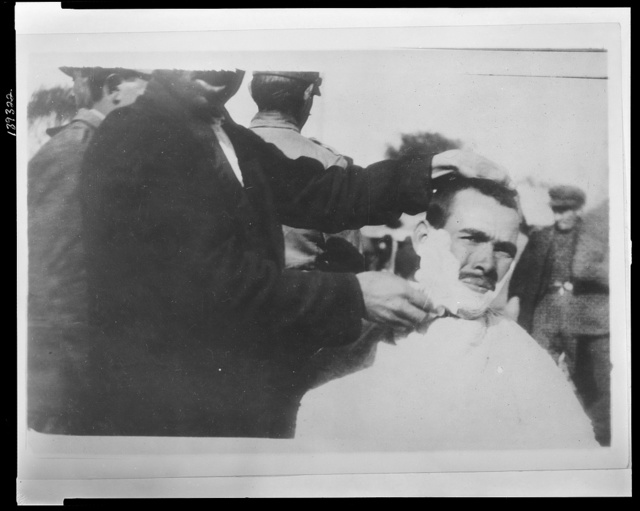 "In ""barbers' row."" There are forty of these crude, improvised barber's chairs in a row along the quay in the Piraeus, the sea port of Athens This victim is being shaved. Is [i.e. when] his hair were being cut the wind would blow his shorn locks down the quay."