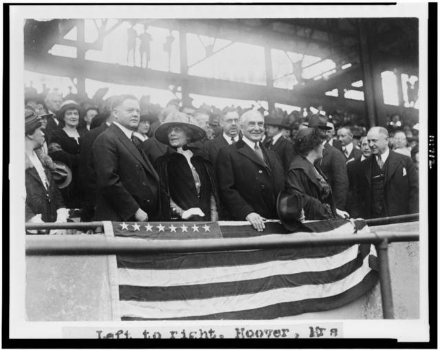 [Left to right: Herbert Hoover, Mrs. Warren G. Harding, Warren G. Harding, Mrs. Herbert Hoover, and H.M. Daugherty, all standing, in grandstand, at baseball game]