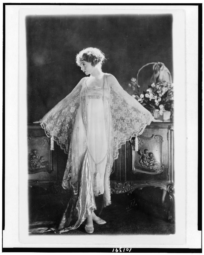 [Lillian Gish, full-length portrait, standing, facing left, wearing pink morning gown of chiffon and lace] / Photo by Bain News Service, New York.