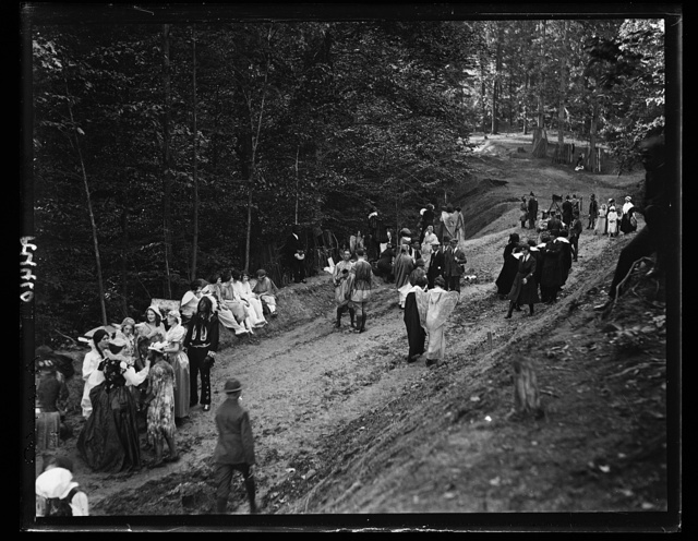 [People in costumes in forest and group with motion picture camera]