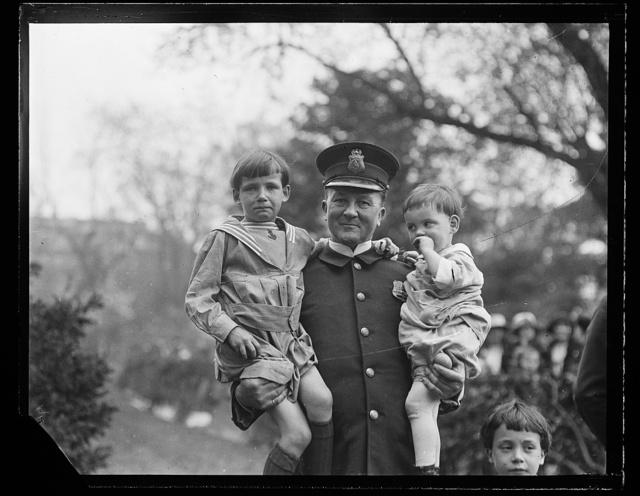 [Police Officer holding children]