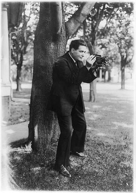 Renato Zanelle, baritone of the Metropolitan Opera, aiming a folding camera