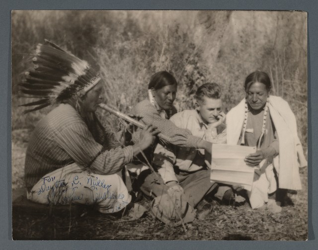 Thurlow Lieurance with three Native American Indians, one of whom plays a courting flute