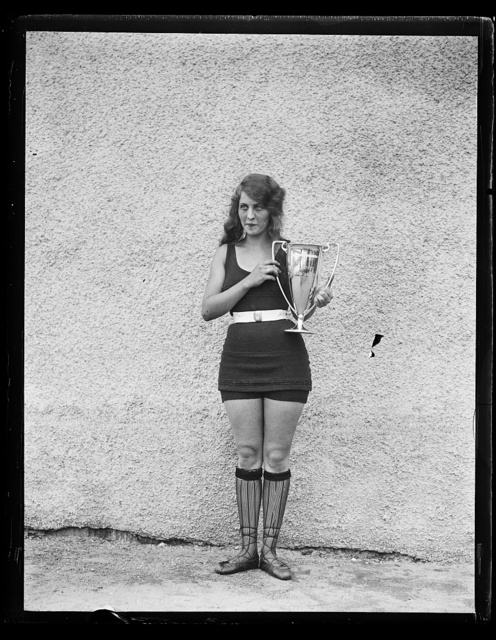 [Woman in bathing suit with trophy cup]