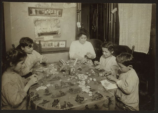 [Woman, two boys, and two girls sitting at a table, making artificial flowers(?)]