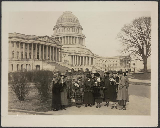 A group of young members of the National Woman's Party before the Capitol. They are about to invade the offices of the senators and congressmen from their states, to ask them to vote for Equal Rights. In the foreground is Miss Anita Pollitzer, secretary of the National Woman's Party, instructing the committee on the method of approach. Left to right: Blanche Alsop, Virginia; Heath Jones, Delaware; Maud Younger, California, legislative Chairman of the Woman's Party; Mrs. Legare Obear, Georgia; Mrs. Burnita Shelton Matthews, Mississippi; Mrs. Anne Archbold, Maine; Miss Wilma Henderson, Massachusetts; Mrs. Emma Brown, Maryland; Mrs. Rowena Dashwood Graves, Colorado.