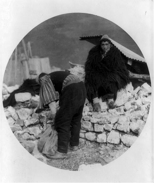 [Albanian man in long-haired cape looking in dismay at ruins of his home, caused by an earthquake in Tepelena, Albania--Another man is sorting stones to repair the damage]
