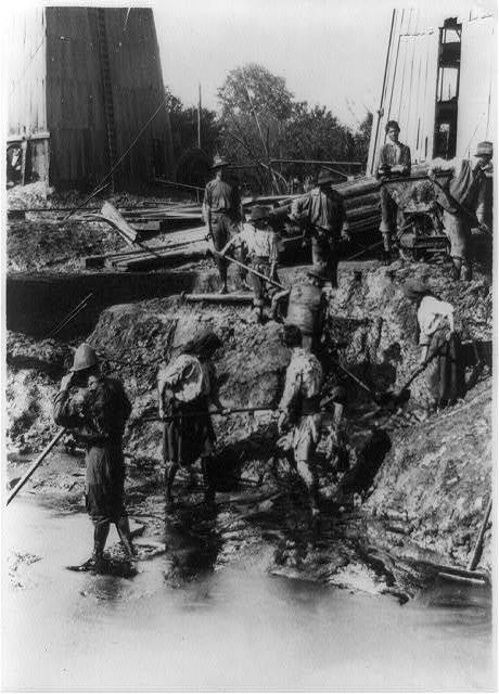 An Earthen Hell. The women dressed in rags stand all day in hot oil shoveling up the refuse to a terrace above them and thence into cars so that not a speck of oil is wasted ...