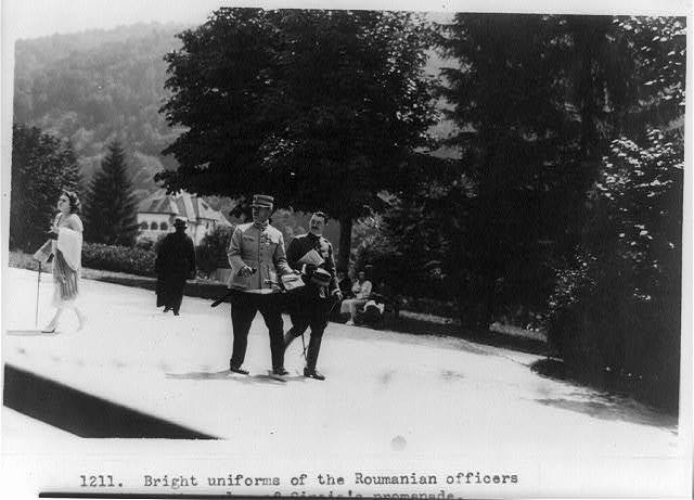 Bright uniforms of the Roumanian officers add to the color of Sinaia's promenade. Rumors have it that corsets and cosmetics often form a part of the officer's equipment in this gay country of the east