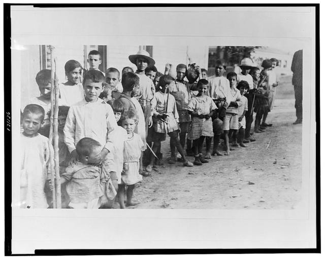 [Greek and Armenian refugee children from Anatolia standing outside one-story building, near Athens, Greece]