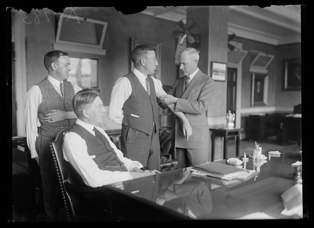 [Group receiving shots; Curtis Wilbur seated at desk]