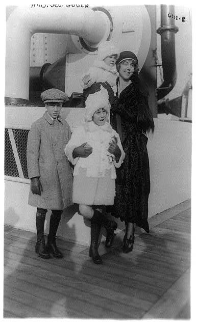 [Guenevere (Sinclair) Gould, full-length portrait, standing on ship, facing right, with three children]