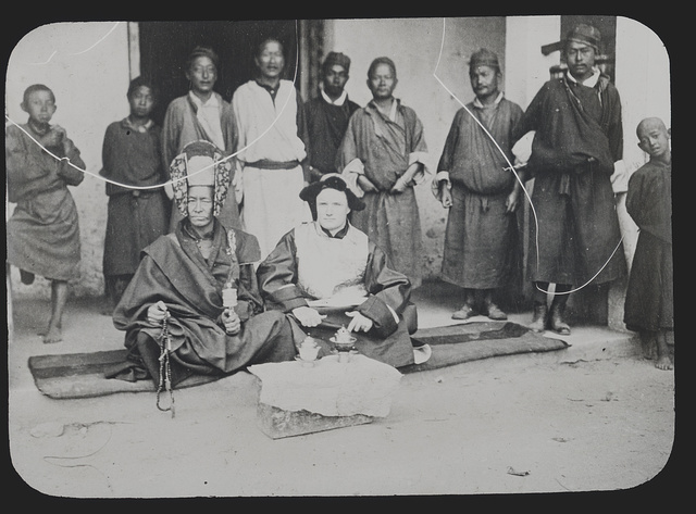 [Lama with headdress and Caucasian man seated in front of nine boys and men, Tibet]