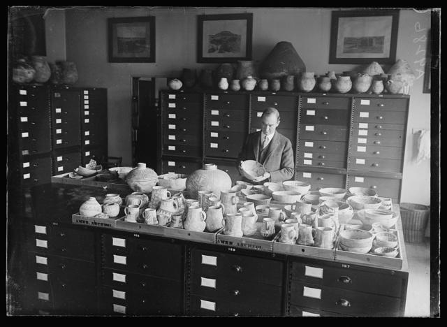 "[Man examining pottery; ""Amer Archeol,"" i.e., American Archaeology?]"