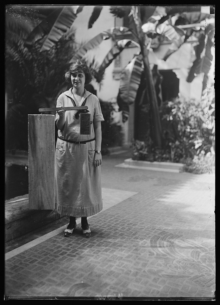 Miss Rosa D. Stone at Pan-Amer. bldg. holding a piece of Guayacan wood, 30'' in diameter which weighs 23 oz. while the Balsa wood with 402 sq. inches of surface weighs the same. Balsa is a recent importation from Latin Amer. and is used as substitute for cork. Already popular not only as filler for life-preservers but as stopper for the modern flask [Washington, D.C.]