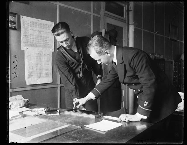 Pay clerk John A. Shaw (right) is shown in the picture taking the fingerprints of Arthur G. Whaley, at Coast Guard headquarters, Wash., D.C.