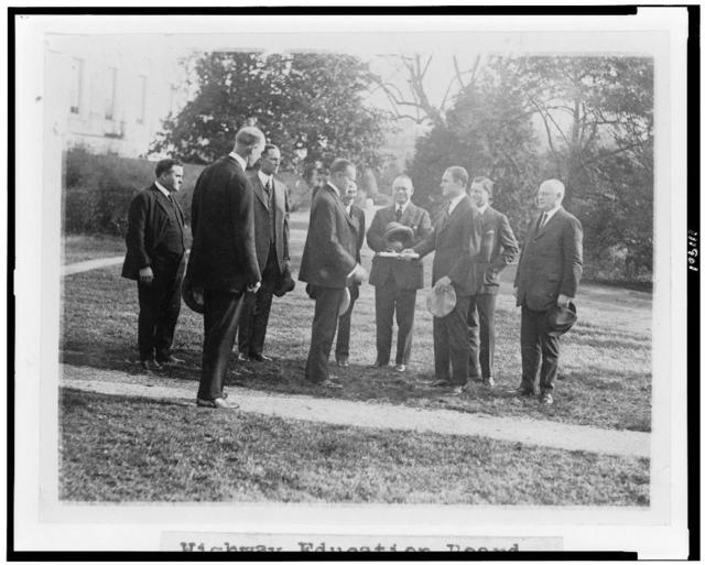 [President Coolidge standing with members of the Highway Education Board on the White House lawn]