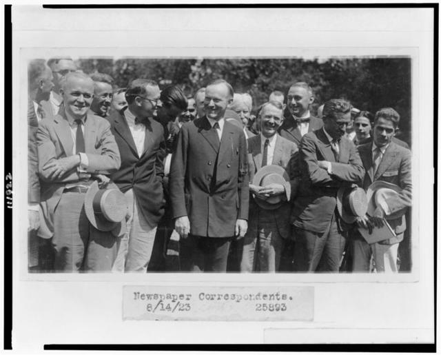 [President Coolidge standing with newspaper correspondents on lawn of the White House]