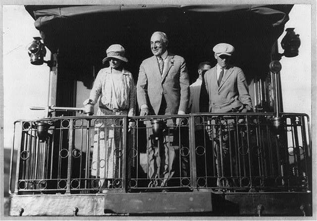 [Warren G. Harding, full length portrait, standing on back of Northern Pacific train, facing left; with wife and Gardener, departing]