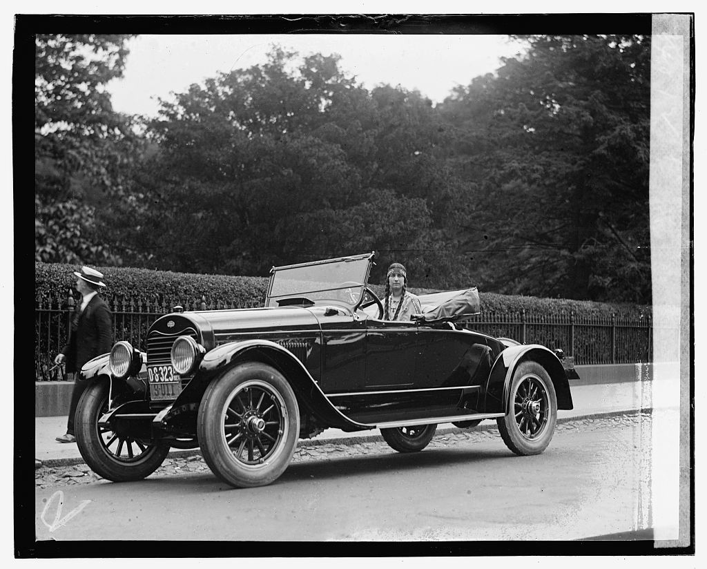 [Woman wearing native american clothing in automobile]