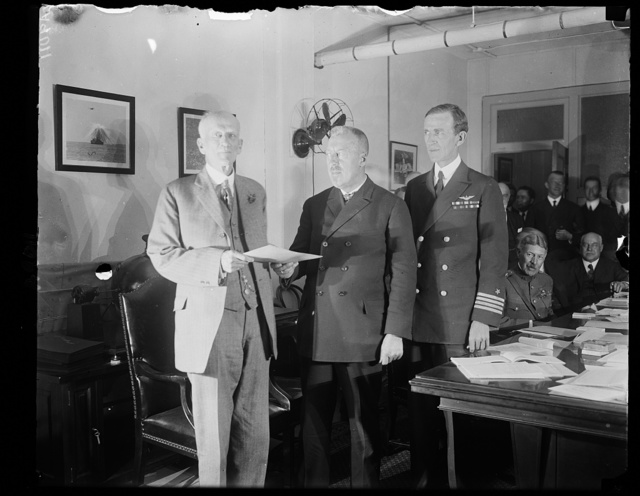 Dr. Hugh Eckener, Builder and Commander of the Z. R-3 giving his official report to Dr. Chas. D. Walcott, chmn. of the Nat'l Advisory Comm. on Aeronautics, upon his arrival in Wash., Oct. 16th. L. to r.: Dr. Walcott, Capt. Eckener, and Capt. Geo. W. Steele, who will command the big ship for the U.S.