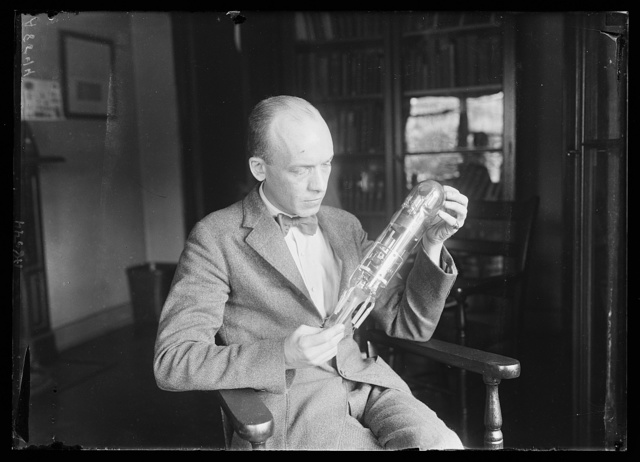 First radio vacuum tube. Carl W. Mitman, Curator of Engineering, US Nat'l Museum, holding what is believed to be the 1st radio tube. It was made in 1898 by D. Mefarlan Moore of NY. Radio waves emanating from this tube ignited a bomb a city block away and blew up a miniature of the Battleship Maine