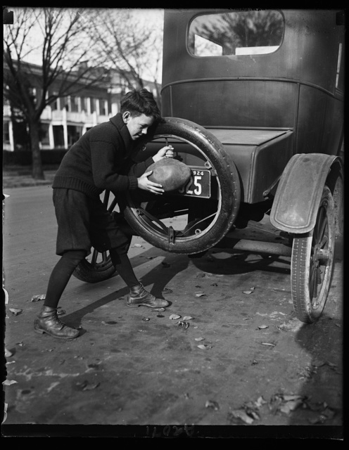 """Flat spare tires are numerous around Wash. These days for the youthful football players who have found an easier way to inflate the pigskin than using their lungs. """"Billy"""" Friel shown inflating his football"""