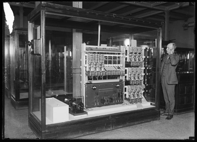 """Here is the """"inside workings"""" of the automatic telephone, located at the Smithsonian Instituion, Wash., being operated by Carl Mitman. The electro magnets do all the work. The current necessary to operate these magnets is supplied by 32 dry batteries located in the box at the left. The motor generator is along side. This machine is capable of operating 50 telephones"""