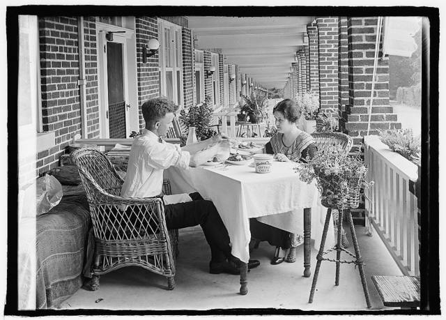 [Man and woman eating at table on front porch of row house]
