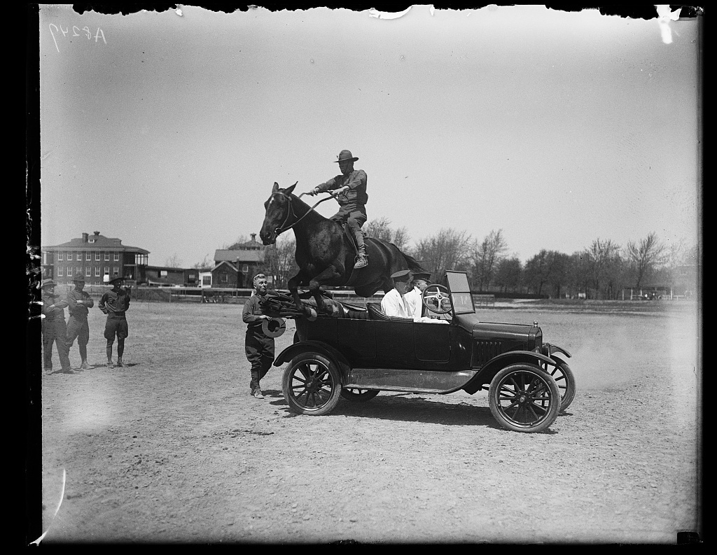 [Man on horse jumping over automobile]
