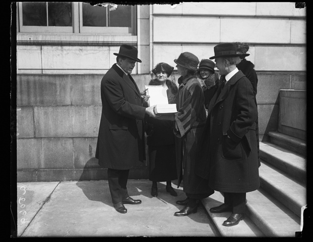 Miss Julienne Sessions, Pres. of the Ohio League of Women Voters, presenting a World Court petition to Sen. F.B. Willis, Chmn. of the Senate Foreign Committee. Left to right: Sen. Willis, Miss Sessions, and Sen. Simon D. Fess of Ohio