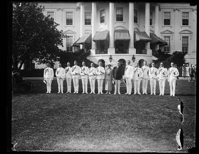 Pres. and Mrs. Coolidge with the W.H.[i.e., White House] military and naval aides, posed on the W.H. lawn just before the garden party to the wounded veterans. At Mrs. C's right: Col. C.O. Sherrill and at the Pres.'s left, Capt. Adolphus Andrews
