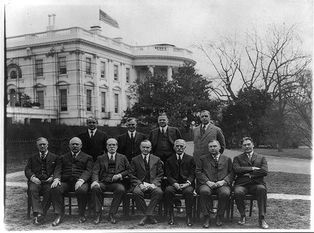 President Coolidge and members of his cabinet posed on the White House Lawn: Secty. of Labor Davis, Secty. of Agriculture Wallace, Secty. of Commerce Hoover, Post Master Gen., Secty. of War Weeks, Secty. of State Hughes, the President, Secty. of Treasury Mellon, Atty. Gen. Stone and Sect. of Navy Wilbur