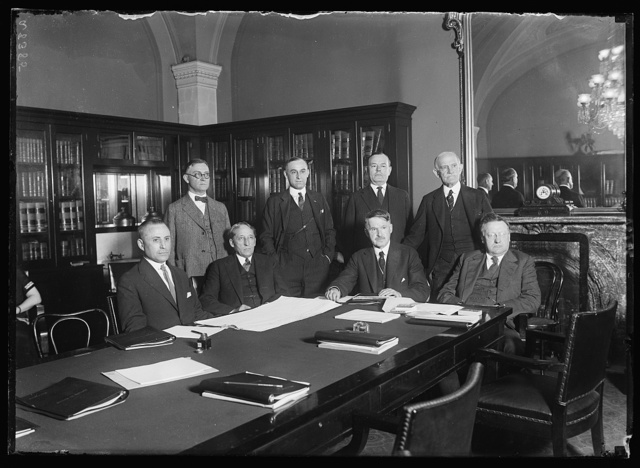 Privileges and elections committee of the Senate now hold hearings on the contest brought by Geo. E.U. Peddy for Senator Earl B. Mayfield's seat. Lft. to rt. seated: Senators M.M. Neely of W.Va., W.H. King, of Utah, S.P. Spencer, of Mo., and James E. Watson, of Ind. standing Lft to rt.: W.F. Zimmerman, Atty. for Mayfield; E.P. Thayer, Sergeant-at-Arms in charge of Recount of Ballots; Wm. McLean, Atty. for Mayfield and Senator Ernst