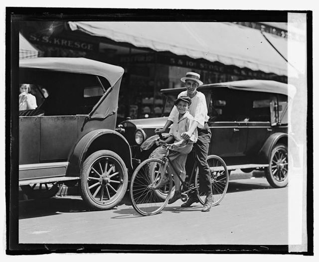 [Street scene, two children on bicycle in front of S.S. Kresge, Washington, D.C.]