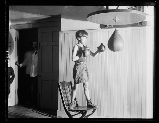 Teddy Roosevelt, Jr., son of the Asst. Secy. of the Navy, punching the bag at the gymnasium at the Racquet Club