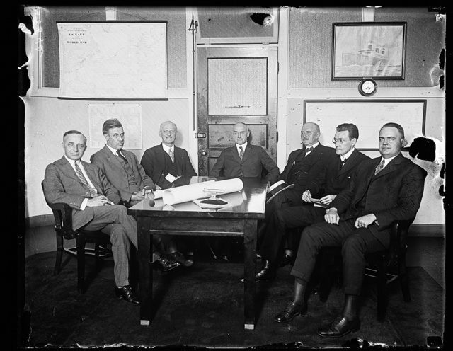 These men will study the problem of placing diesel engines in the shipping board vessels. Lft. to rt. around the table: A. Conti, Consulting Engineer to Adm. Benson; J.F. Nichols, Chief Engineer, Newport News Shipbuilding Co.; Adm. H. I. Cone, Asst. to Pres. of the Fleet Corportation, Chmn.; Adm. W. S. Benson; Capt. Chas. A McAllister, v-p Amer. Bu. of Shipping; William Francis Gibbs, Pres. Gibbs Bros. Inc.; and Maj. W. D. Styer, Engineer Corps, USA