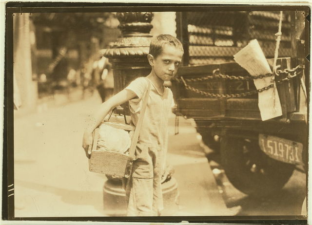 Tommie, very young shiner, Canal Street, New York City. Some of these youngsters do not know their ages nor how much they earn. July 25, 1924.  Location: New York, New York (State)