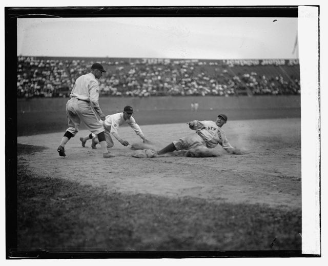 Yankees catcher Wally Schang slides safely into 3rd base in second game. Senators 3rd baseman is Ossie Bluege and pitcher backing up play is Firpo Marberry. Senators won 2nd game 7-2 (baseball)