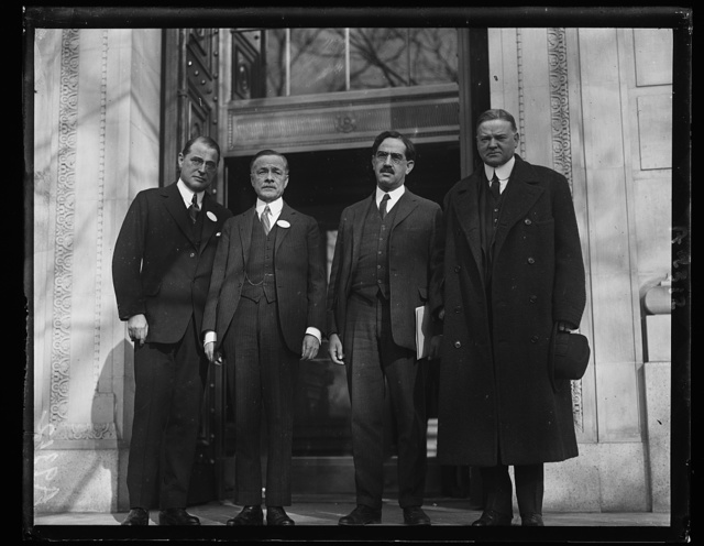 A national conference of business men to inquire into the costs and methods of distributing merchandise of all kinds was opened in Washington today, January 14th, at the Chamber of Commerce of the United States. Prominent men from all over the country attended the first session which was addressed by the Secretary of Commerce, Herbert Hoover, who outlined from the national viewpoint the problems in distributing. In the group, left to right, T.F. Whitmarsh of New York; General J.J. Carty, Vice-President of the American Telephone and Telegraph Company; C.L. Alsberg, Leland Stanford University of California and Herbert Hoover, Secretary of Commerce