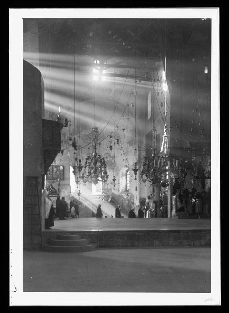 [Bethlehem. Church of the Nativity. Dark interior lit by sun rays]