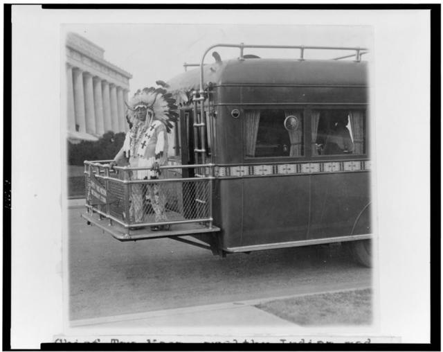 Chief Two Moon, wealthy Indian medicine man from Waterbury, Conn., photographed at the Lincoln Memorial on the observation platform of his palatial touring bus ...
