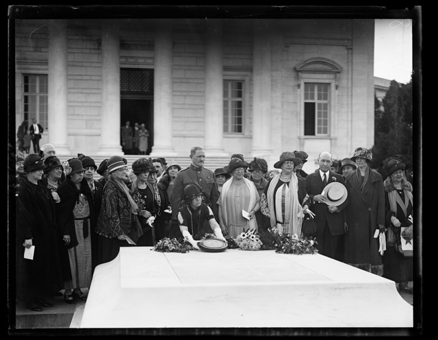 General John J. Pershing joined with members of the Service Star Legion in paying homage to the World War dead at Arlington National Cemetery before the Tomb of the Unknown Soldier on Tuesday afternoon, May 26th. Mrs. Henry F. Baker of Hyde, Md., placed a bronze insignia of the Order in the Trophy Room of the Amphitheatre. The picture shows Mrs. Florence M. Thorpe of Lynn, Mass. laying the insignia upon the tomb. General Pershing is [...] directly behind Mrs. Thorpe. At the General's left is [...] Baker, then Mrs. [Max?] Mayer of Des Moines, Iowa and General [...] T. Hines, Director of the Veterans Bureau