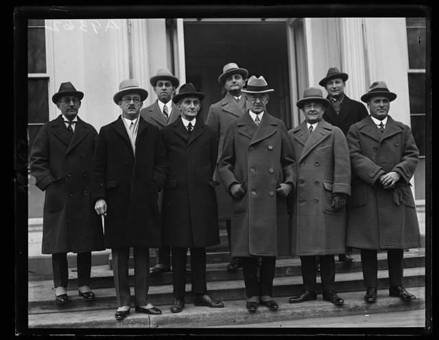 Governor Towner of Porto [sic] Rico with [..]ers of th [...] Porto [sic] Rican cabinet as they appeared at the White [...] to discuss legislative matters with President Coolidge. In the [...]t row, (left to right) Gonzales Mena, Senator-Elect; M. Guerra Mondrago [...] speaker of the House; Felix Cordova Devila, resident Governor Horace M. Towner; Capt. R.J. Van Densen, Secretary to the Gov.; Dr. Ped[...] N. Oatix, Commissioner of Health. Back row: (left to right) Hon. E. [...] Bird, Rep.; Asst. Attorney General M.A. Moraz and Commissioner of the Interior Guillermo Esteves