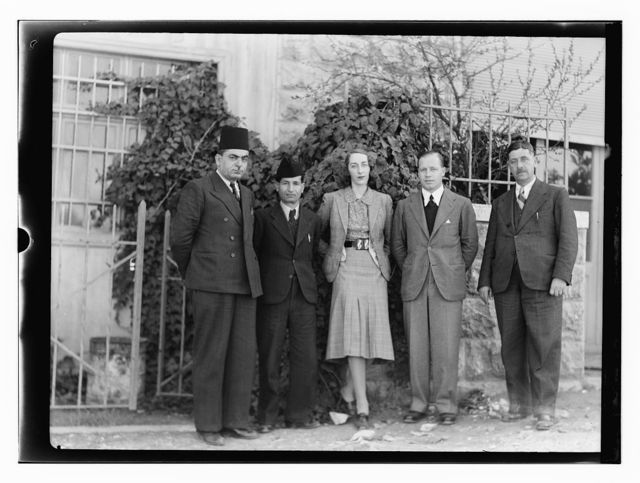 [Group portrait of woman standing with four men in front of building]