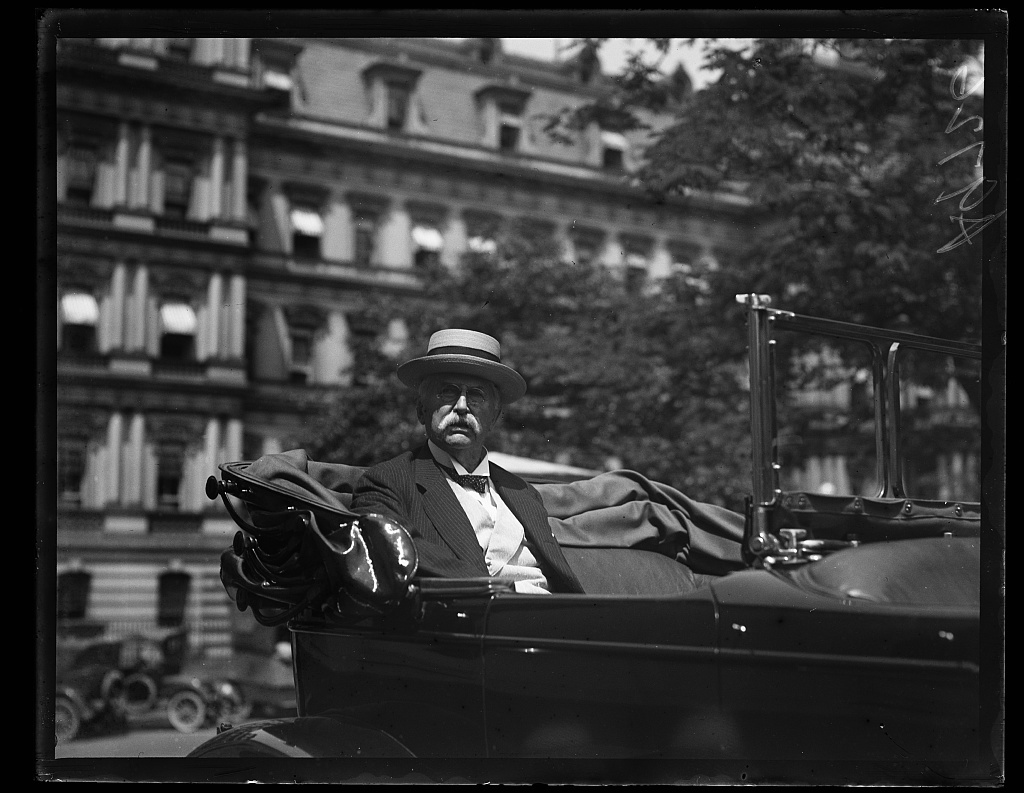 [Man in automobile at White House; State, War and Navy Building in background. Washington, D.C.]