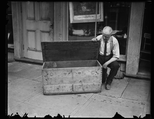 [Man with antique wooden chest]