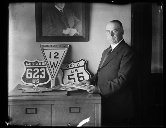 [Man with highway signs]