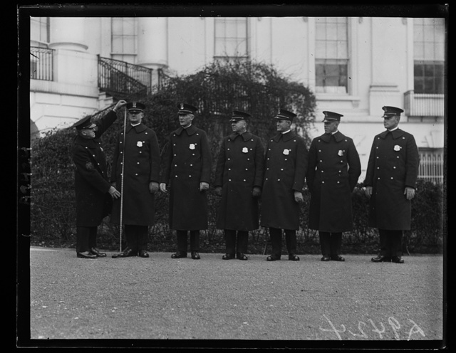 New White House police must be tall. Six new six-footers have been added to the White House police force by the Congressional Deficiency bill of last December. Regulations require that they be six feet and over. The picture shows Sergeant Dalrymple measuring R.G. Ford, a new officer, measuring 6 feet 2 inches. In the group, left to right: R.G. Ford, P.A. McDuffie, Dick Ballard, W.M. Haywood, P.E. Allen and B.B. Bradley